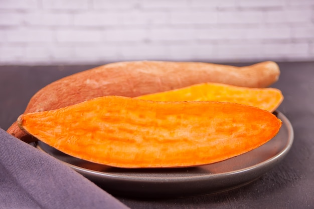 Raw sweet potatoes on the black table.
