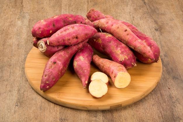 木製スペースのクローズアップで生のサツマイモ。新鮮な野菜。