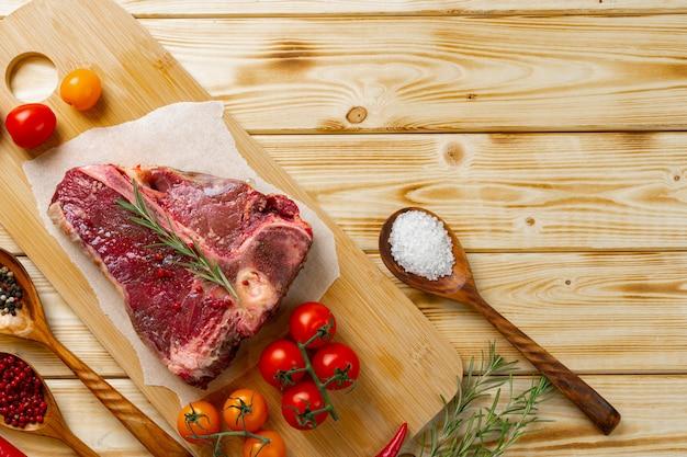 テーブルの上の新鮮な野菜とローズマリーの生tボーン肉をクローズアップ。