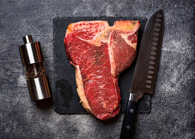 Raw t-bone steak on slate board
