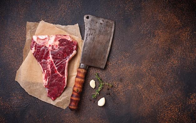 Сырой стейк на косточке с ножом для мясника