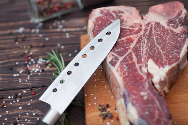 Raw t-bone steak with rosemary, pepper and olive oil on a cutting board prepared for cooking