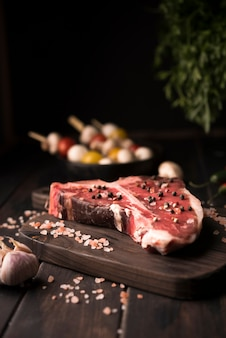 Raw t-bone steak with salt and pepper