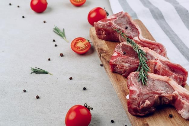 Raw t-bone steak on wooden cutting board on wooden table