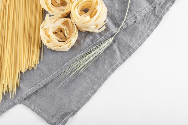 회색 식탁보에 원시 tagliatelle 및 스파게티 파스타.