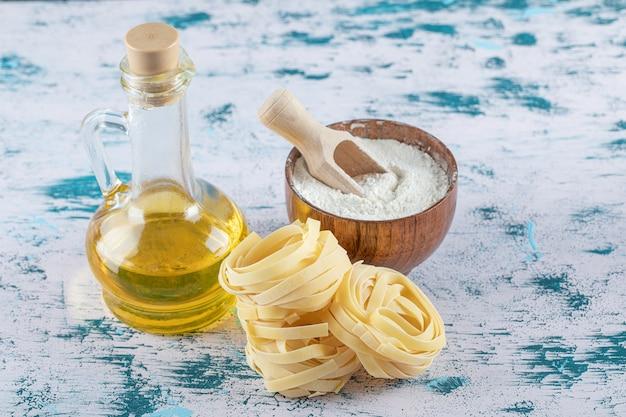Nidi di tagliatelle crude, olio d'oliva e ciotola di farina sulla superficie colorata.