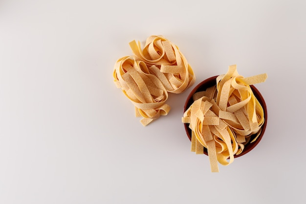 Raw tagliatelle pasta in the bowl top view on white surface
