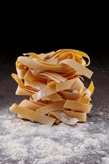Raw tagliatelle pasta and flour on black surface