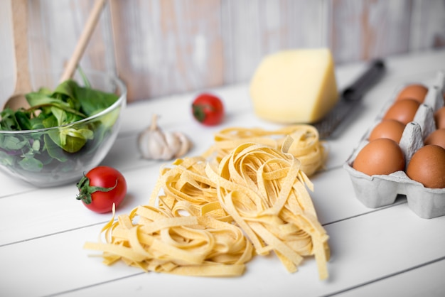 Raw tagliatelle pasta and ingredient over wooden table