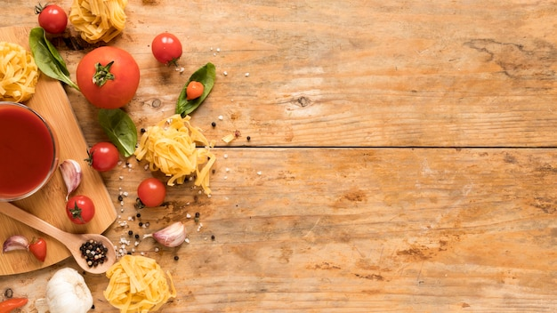 Raw tagliatelle pasta near it's ingredients and tomato sauce over textured wooden background