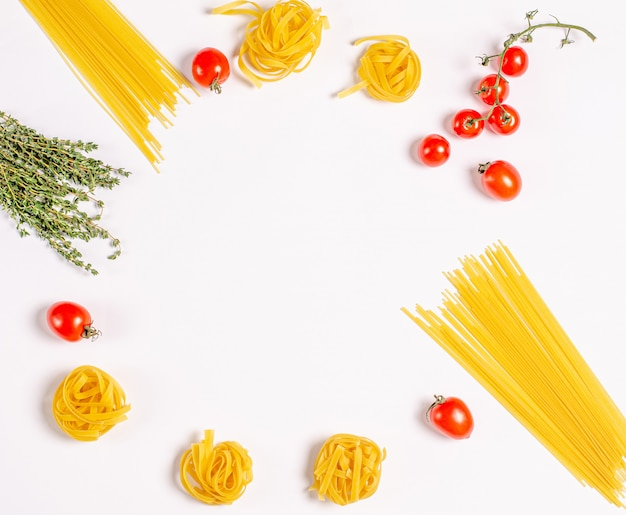 Raw tagliatelle pasta, spaghetti with tomatoes, thyme, round frame with copy space for texat, flat lay.