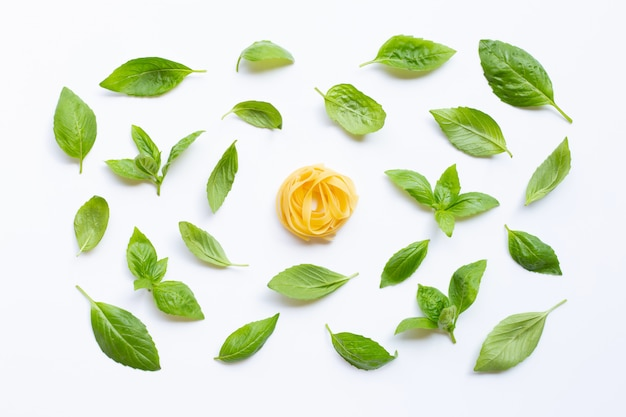 Raw tagliatelle pasta with basil leaves on white
