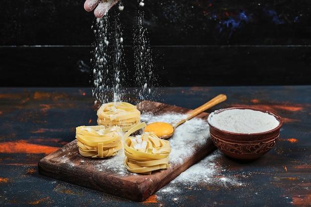 Tagliatelle crude su tavola di legno con ciotola di polvere.
