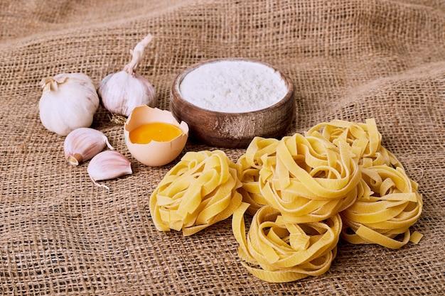 Raw tagliatelle pasta on a wool cloth.