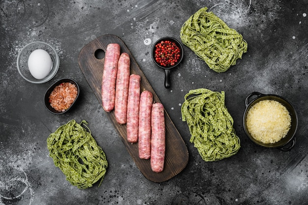 Raw tagliatelle sausages ingredients set, on black dark stone table background, top view flat lay