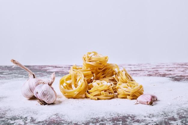Tagliatelle crude con aglio su superficie grigia.
