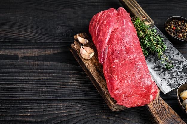 Сырая вырезка из говядины для стейков, филе миньон на деревянной разделочной доске с ножом для мясника. черный деревянный фон. вид сверху. скопируйте пространство.