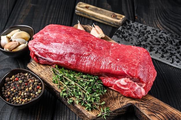 Сырое мясо телятины для стейков, филе миньон на деревянной разделочной доске с ножом для мясника.