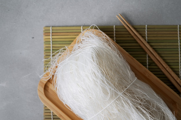 Raw thin rice noodles on bamboo dish on stone surface with sticks