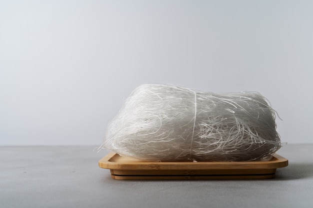 Raw thin rice noodles on bamboo dish with chopsticks on stone surface with copy space.