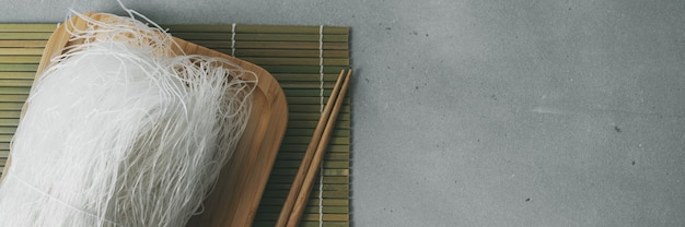 Raw thin rice noodles on bamboo plate on stone surface with sticks. long wide banner.