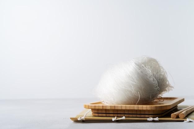 복사 공간 돌 표면에 젓가락으로 대나무 접시에 원시 얇은 쌀 국수.