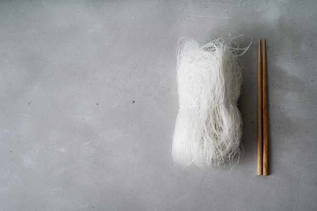 Raw thin rice noodles on stone surface with chopsticks.