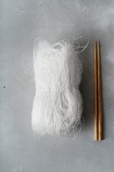 Raw thin rice noodles with sticks on stone surface. flat lay