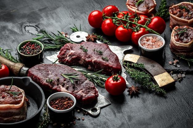 Сырые три стейка говядины на мясном ноже с темным фоном специй. вид сверху.