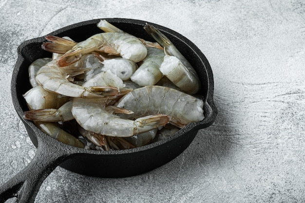 Raw tiger prawns set, in cast iron frying pan, on gray stone background