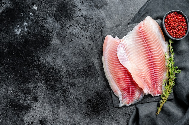 Raw tilapia fillet on a chopping board with thyme and pink pepper. black background. top view. copy space.