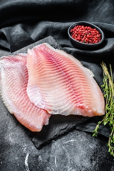 Raw tilapia fillet on a chopping board with thyme and pink pepper. black background. top view.