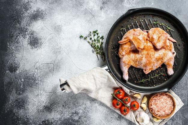 Сырой табак курица в сковороде. серый фон вид сверху. пространство для текста