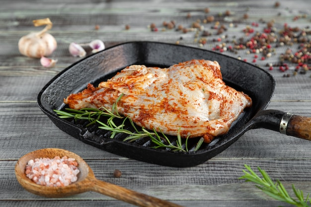 Raw tobacco chicken in spices in black grill pan, pepper