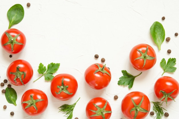 Raw tomatoes, herbs and black pepper on a light concrete background