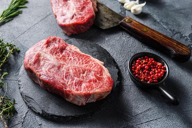 生のトップブレードフラットアイアンカット、黒いスレート、および灰色の石の表面の背景の側面図上のハーブトマトペッパーコーンと肉屋の包丁大理石の牛肉をクローズアップします。