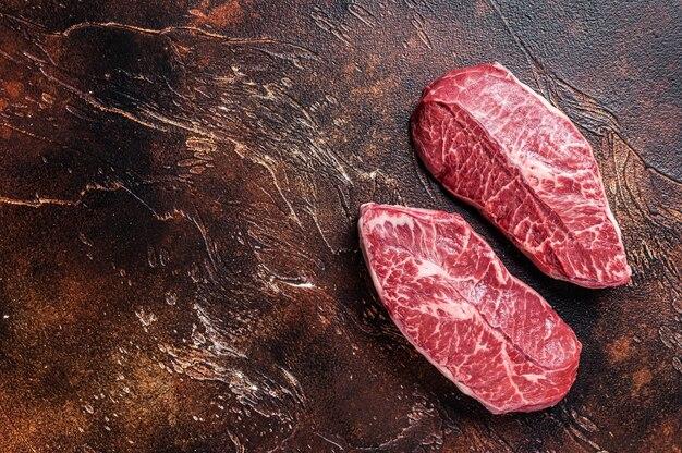 정육점 테이블에 있는 raw top blade 또는 평평한 철 쇠고기 고기 스테이크. 어두운 배경입니다. 평면도. 공간을 복사합니다.