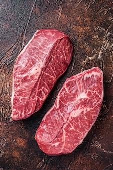肉屋のテーブルに生のトップブレードまたはフラットアイアンビーフミートステーキ。上面図。