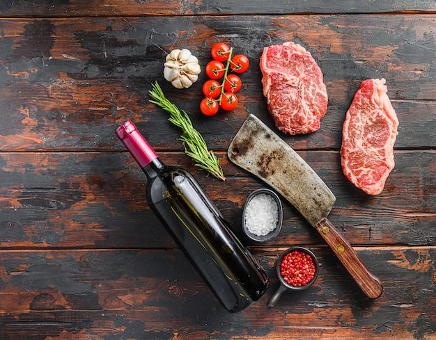 Сырые стейки с верхним лезвием с приправой из трав и мясником возле бутылки красного вина над старым темным деревянным столом, место для текста.