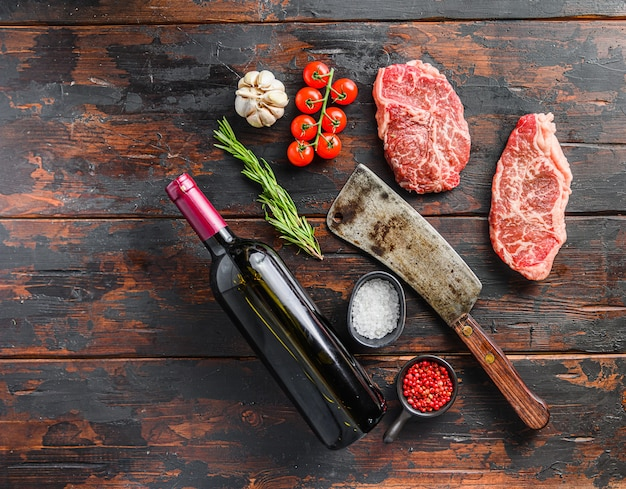 Raw top blade steaks with herbs seasoning and butcher knife near red wine bottle over old dark wooden table top view, space for text.