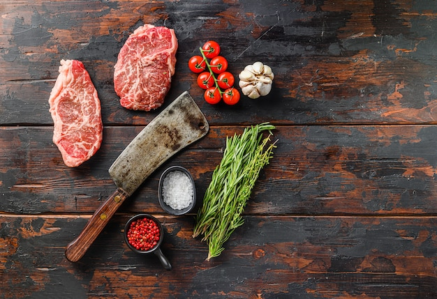 Raw top blade steaks with herbs seasoning and butcher knife over old dark wooden table top view, space for text.