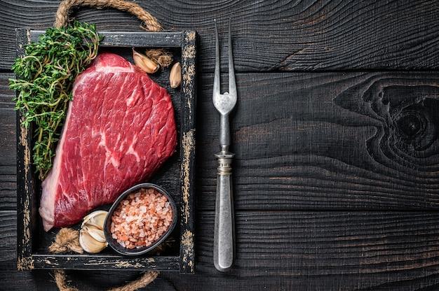 生のトップサーロインキャップビーフカットミートステーキまたはピカーニャをハーブ入りの木製トレイに入れます。黒の木製テーブル。上面図。