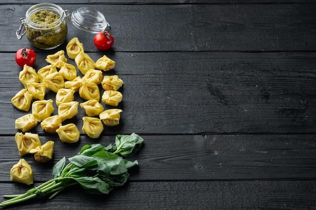 검은 나무 테이블에 바질과 소나무 페스토와 원시 tortellini