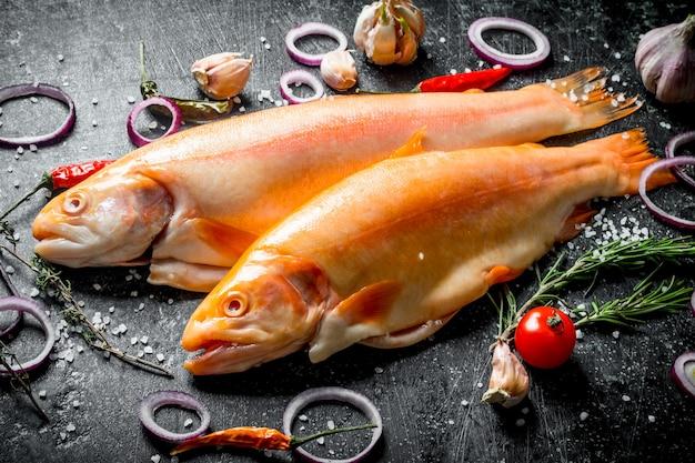 暗い木製のテーブルに刻んだタマネギ、ニンニク、唐辛子と生のマスの魚