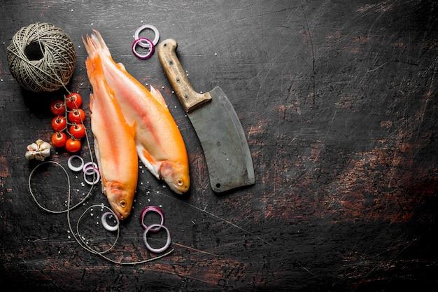 Сырая форель со старым шпагатом и ножом на темном деревенском столе
