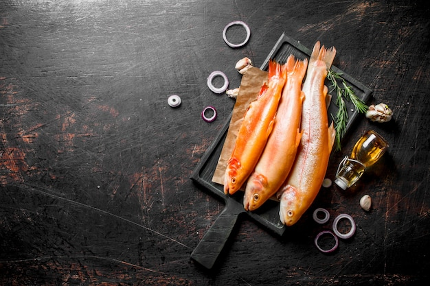 어두운 시골 풍 테이블에 양파 링과 마늘을 곁들인 원시 송어 물고기