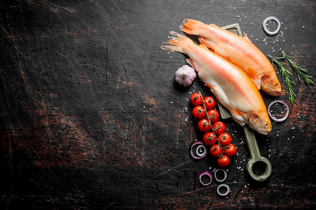 Сырая форель с луковыми кольцами, помидорами, розмарином и чесноком на деревенском столе.
