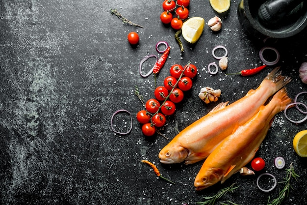 Сырая форель с помидорами, кольцами лимона и лука на деревенском столе