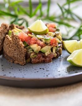 Тартар из сырого тунца и авокадо, подается с крекерами из ржаного хлеба и тартаром из рыбы для гурманов с лаймом
