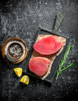 Сырое филе тунца на разделочной доске с розмарином, лимоном и специями на темном деревенском столе.